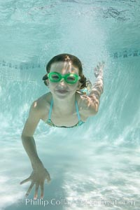 A young girl swimming with goggles in a bright swimming pool