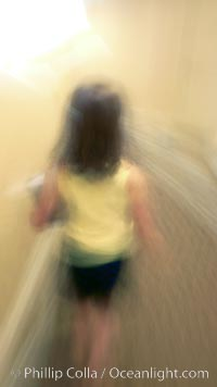 Girl walks down hotel corridor at night, carrying ice bucket, abstract blur time exposure