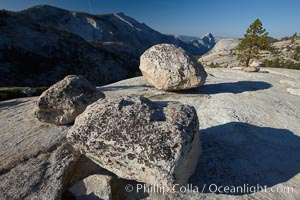 Glacial erratic boulders atop Olmsted Point, with the massive granite monoliths Half Dome and Clouds Rest in the background. Erratics are huge boulders left behind by the passing of glaciers which carved the granite surroundings into their present-day form.  When the glaciers melt, any boulders and other geologic material that it was carrying are left in place, sometimes many miles from their original location, Yosemite National Park, California