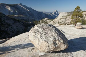 Glacial erratic boulder atop Olmsted Point, with the massive granite monoliths Half Dome and Clouds Rest in the background. Erratics are huge boulders left behind by the passing of glaciers which carved the granite surroundings into their present-day form.  When the glaciers melt, any boulders and other geologic material that it was carrying are left in place, sometimes many miles from their original location, Yosemite National Park, California