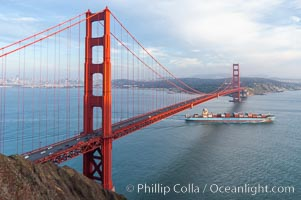A container ship leaves San Francisco Bay, passing under the Golden Gate Bridge, viewed from the Marin Headlands with the city of San Francisco in the distance.  Late afternoon