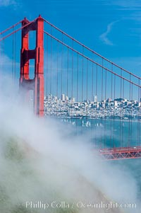 San Franciscos infamous summer fog overtakes the Golden Gate Bridge, viewed from the Marin Headlands with the city of San Francisco visible in the distance