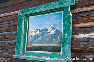 Teton Range reflection, in window of old barn in Grand Teton National Park