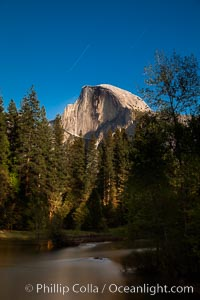 Half Dome and star trails, at night, viewed from Sentinel Bridge, illuminated by the light of the full moon, Yosemite National Park, California