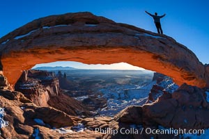 Mesa Arch, Utah.  An exuberant hiker greets the dawning sun from atop Mesa Arch, Island in the Sky, Canyonlands National Park
