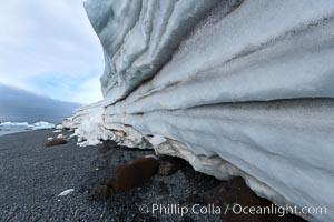 Horizontal striations and layers in packed snow, melting and overhanging, seen from the edge of the snowpack, along a rocky beach, Brown Bluff