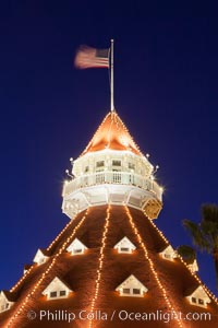 Hotel del Coronado with holiday Christmas night lights, known affectionately as the Hotel Del. It was once the largest hotel in the world, and is one of the few remaining wooden Victorian beach resorts. It sits on the beach on Coronado Island, seen here with downtown San Diego in the distance. It is widely considered to be one of Americas most beautiful and classic hotels. Built in 1888, it was designated a National Historic Landmark in 1977