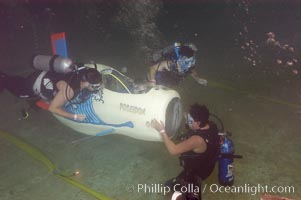 Student engineers prepare a human-powered submarine for an underwater time trial.  The submarines pilot and source of power is visible in the cockpit, and breathes on SCUBA while operating the sub.  The submersible was designed, built and operated by High Tech High School (San Diego, California) engineering students, Offshore Model Basin, Escondido