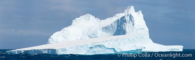 Iceberg panoramic photo.  Iceberg, ocean, light and clouds. Light plays over icebergs and the ocean near Coronation Island