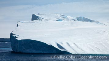 Iceberg and snow-covered coastline, Antarctic Sound