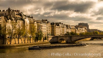 River Seine, barge and Ile Saint-Louis, sunrise, Paris. Ile Saint-Louis, is one of two natural islands in the Seine river, in Paris, France. The island is named after King Louis IX of France (Saint Louis). The island is connected to the rest of Paris by bridges to both banks of the river and by the Pont Saint Louis to the Ile de la Cite