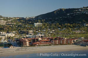 La Jolla Shores Beach, with the La Jolla Shores Hotel fronting the flat sand beach.  Mount Soledad rises in the background