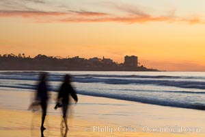 Tourists walk along La Jolla Shores beach at sunset.  Point La Jolla is visible in the distance, Scripps Institution of Oceanography