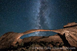 Landscape Arch and Milky Way galaxy.  Stars rise over Landscape arch at night, filling the Utah sky, while the arch is gently lit by a hiker's light, Arches National Park