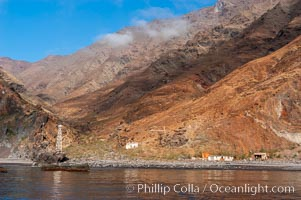 Guadalupe Islands steep cliffs tower above a small fishing shack, lighthouse, old chapel and prison near the north end of Guadalupe Island (Isla Guadalupe)