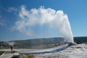 A visitor videotapes the eruption of Lion Geyser, with Old Faithful Inn visible in the distance.  Lion Geyser, whose eruption is preceded by a release of steam that sounds like a lion roaring, erupts just once or a few times each day, reaching heights of up to 90 feet.  Upper Geyser Basin, Yellowstone National Park, Wyoming