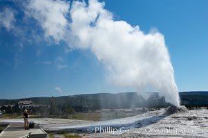 A visitor videotapes the eruption of Lion Geyser, with Old Faithful Inn visible in the distance.  Lion Geyser, whose eruption is preceded by a release of steam that sounds like a lion roaring, erupts just once or a few times each day, reaching heights of up to 90 feet.  Upper Geyser Basin. Upper Geyser Basin, Yellowstone National Park, Wyoming, USA