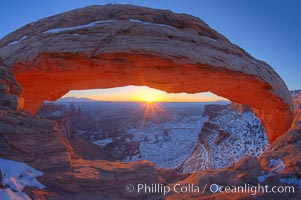 Mesa Arch spans 90 feet and stands at the edge of a mesa precipice thousands of feet above the Colorado River gorge. For a few moments at sunrise the underside of the arch glows dramatically red and orange, Island in the Sky, Canyonlands National Park, Utah