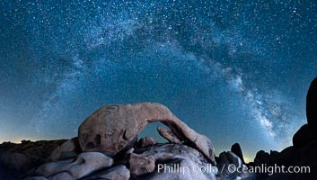 The Milky Way galaxy arcs above Arch Rock, panoramic photograph, cylindrical projection, Joshua Tree National Park, California