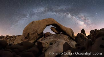 Milky Way during Full Lunar Eclipse over Arch Rock, Joshua Tree National Park, April 4 2015.  The arch and surrounding landscape are illuminated by the faint light of the fully-eclipsed blood red moon.  Light from the sun has passed obliquely through the Earth's thin atmosphere, taking on a red color, and is then reflected off the moon and reaches the Earth again to light the arch.  The intensity of this light is so faint that the Milky Way can be seen clearly at the same time. Joshua Tree National Park, California, USA, natural history stock photograph, photo id 30717