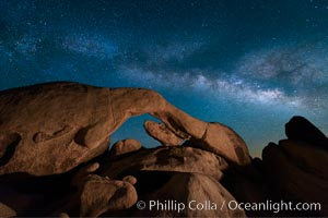 The Milky Way stretches across the sky above Arch Rock in Joshua Tree National Park