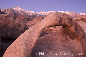 Mobius Arch, the Alabama Hills and the Sierra Nevada Range at sunrise, pink early morning light. Alabama Hills Recreational Area, California, USA