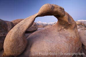 Mobius Arch at sunrise, with Mount Whitney (the tallest peak in the continental United States), Lone Pine Peak and snow-covered Sierra Nevada Range framed within the arch.  Mobius Arch is a 17-foot-wide natural rock arch in the scenic Alabama Hills Recreational Area near Lone Pine, California