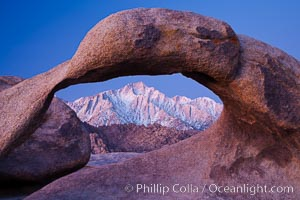 Mobius Arch at sunrise, framing snow dusted Lone Pine Peak and the Sierra Nevada Range in the background. Also known as Galen&#39;s Arch, Mobius Arch is found in the Alabama Hills Recreational Area near Lone Pine