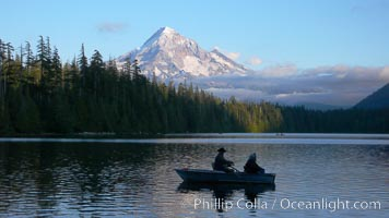 Mount Hood rises above Lost Lake, two old people fishing from a small boat, sunset, Mt. Hood National Forest, Oregon