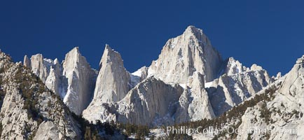 Mt. Whitney is the highest point in the contiguous United States with an elevation of 14,505 feet (4,421 m).  It lies along the crest of the Sierra Nevada mountain range.  Composed of the Sierra Nevada batholith granite formation, its eastern side (seen here) is quite steep.  It is climbed by hundreds of hikers each year