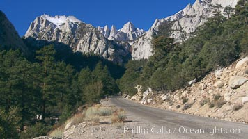 Mount Whitney rises above the Whitney Portal Road which leads to the trailhead from which Mt. Whitney is usually approached by climbers.  Mt. Whitney is the highest point in the contiguous United States with an elevation of 14,505 feet (4,421 m).  It lies along the crest of the Sierra Nevada mountain range.  Composed of the Sierra Nevada batholith granite formation, its eastern side (seen here) is quite steep.  It is climbed by hundreds of hikers each year