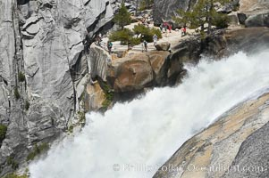 The brink of Nevada Falls, with hikers visible at the precipice. Nevada Falls marks where the Merced River plummets almost 600 through a joint in the Little Yosemite Valley, shooting out from a sheer granite cliff and then down to a boulder pile far below, Yosemite National Park, California