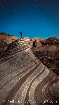 Exuberant hiker atop the Fire Wave, at night, stars and the evening sky, Valley of Fire State Park