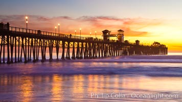 Oceanside Pier at sunset, clouds with a brilliant sky at dusk, the lights on the pier are lit. Oceanside Pier, Oceanside, California, USA