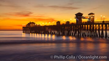 Oceanside Pier at sunset, clouds with a brilliant sky at dusk, the lights on the pier are lit