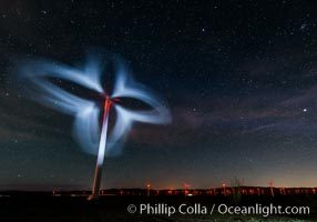 Stars rise above the Ocotillo Wind Turbine power generation facility, with a flashlight illuminating the turning turbine blades
