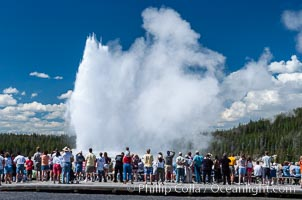 A crowd gathers to watch the worlds most famous geyser, Old Faithful, in Yellowstone National Park, Upper Geyser Basin