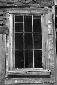 Battered old window and frame on whats left of a small private home