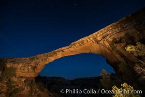 Owachomo Bridge at sunset, stars and blue sky.  Owachomo Bridge, a natural stone bridge standing 106' high and spanning 130' wide,stretches across a canyon with the Milky Way crossing the night sky, Natural Bridges National Monument, Utah
