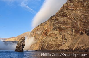 Pilot Rock (Roca Pilote), a undersea spire which extends 100 out of the water, stands below the immense seacliffs and morning clouds at the north end of Guadalupe Island (Isla Guadalupe), far offshore of the Baja California peninsula