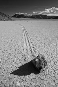 Sailing stone on the Death Valley Racetrack playa.  The sliding rocks, or sailing stones, move across the mud flats of the Racetrack Playa, leaving trails behind in the mud.  The explanation for their movement is not known with certainty, but many believe wind pushes the rocks over wet and perhaps icy mud in winter. Racetrack Playa, Death Valley National Park, California, USA, natural history stock photograph, photo id 25333