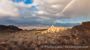 Rainbow and clearing storm clouds, sunrise light on Manly Beacon, Zabriskie Point, Death Valley National Park, California