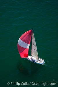 Sailboat under sail on the open ocean, spinnaker set and filled with wind