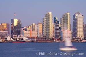 San Diego city skyline at dusk, viewed from Harbor Island, a sailboat cruises by in the foreground, the Star of India at left