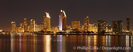 San Diego city skyline at night, showing the buildings of downtown San Diego reflected in the still waters of San Diego Harbor, viewed from Coronado Island.  A panoramic photograph, composite of seven separate images.,  Copyright Phil Colla, image #22254, all rights reserved worldwide.
