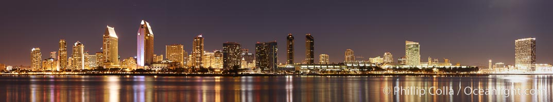 San Diego city skyline at night, showing the buildings of downtown San Diego reflected in the still waters of San Diego Harbor, viewed from Coronado Island.  A panoramic photograph, composite of five separate images