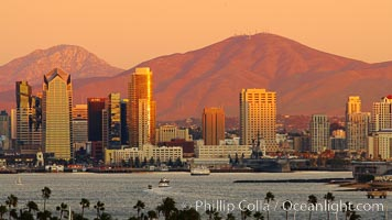 San Diego city skyline, showing the buildings of downtown San Diego rising above San Diego Harbor, viewed from Point Loma at sunset, with mountains of the Cleveland National Forest rising in the distance