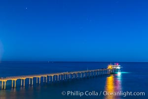 Scripps Institution of Oceanography Research Pier at night, lit with stars in the sky, old La Jolla town in the distance