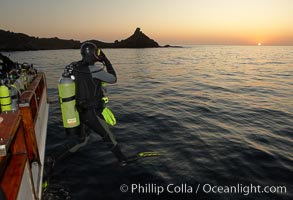 A SCUBA diver leaps into the water, from boat Horizon, into the kelp forest and rich waters of San Clemente Island, China Hat Point, Balanced Rock, sunrise. San Clemente Island, California, USA, natural history stock photograph, photo id 23557