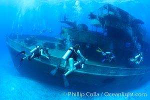 SCUBA divers on the wreck of the USS Kittiwake, sunk off Seven Mile Beach on Grand Cayman Island to form an underwater marine park and dive attraction